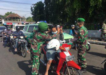Pemberian masker dari Korem 072/Pamungkas kepada pengguna jalan di Denggung, Sleman. (Foto: Affan)