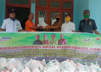 Disaksikan oleh pihak PTPN-4, Camat Hatonduhan menyerahkan bantuan kepada yang mewakili warga (Foto: RS-LNT)