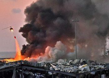 Sebuah helikopter berusaha memadamkan api dalam ledakan yang terjadi di pelabuhan Beirut, ibu kota Lebanon, pada 4 Agustus 2020.(STR via AFP)